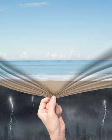 Woman hand pulling open calm sea beach curtain covering stormy city. Stockfoto