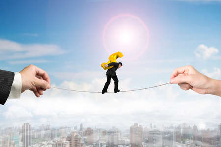 Businessman carrying golden dollar sign, balancing on tightrope with man and woman hands holding two sides, on sun sky city landscape background. 版權商用圖片