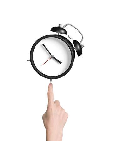 dedo �ndice: El dedo �ndice humano se�ala en el reloj de alarma, sobre fondo blanco. Foto de archivo
