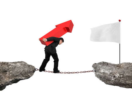 hard work ahead: Businessman carrying red arrow sign balancing on rusty chain, walking to white flag on cliff, with white background. Stock Photo