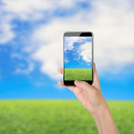 button grass: Female hand holding smart phone, with thumb pushing button, front view, on sky clouds grass background. Stock Photo