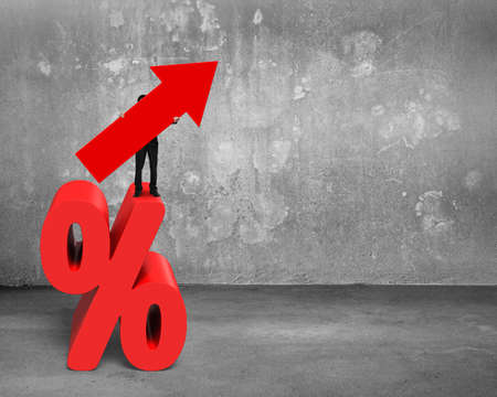 percentage sign: Businessman holding red arrow symbol standing on percentage sign, on concrete wall and floor background.