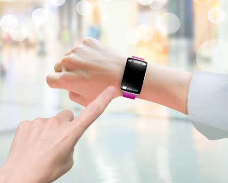 wearable: Female index finger pointing smart watch with blank black glass bent touchscreen, on blurred background Stock Photo