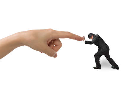 conflicts: Small businessman pushing against big hand forefinger, isolated on white.