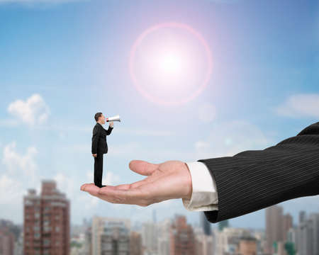 squabble: Small businessman using speaker shouting on big male hand palm open, with sunny sky cityscape background.