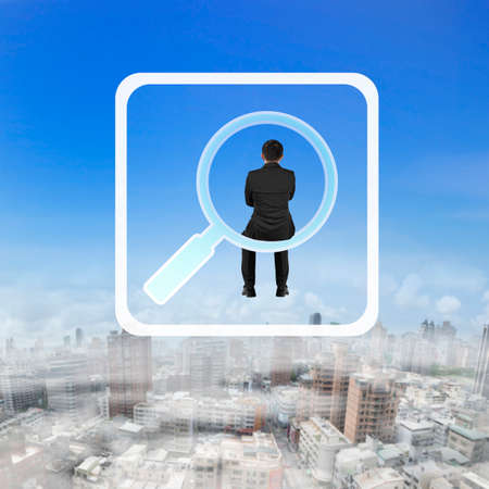 rear view: Rear view of businessman sitting on searching app icon, on blue sky cityscape background.