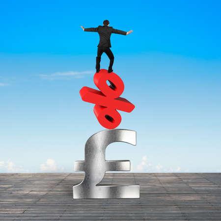 libra esterlina: El hombre de negocios que balancea en signo de porcentaje rojo y símbolo de la libra esterlina, con fondo de cielo azul.