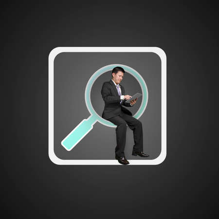 keywords link: Businessman sitting on searching app icon and using smart pad, on black background. Stock Photo
