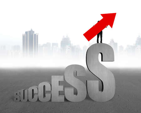 business symbol: Man holding red arrow up sign, standing on concrete dollar sign with success text stairs, on gray city skyline background. Stock Photo