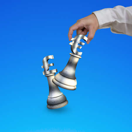euro sign: Human hand playing money currency symbol chess pieces, with euro sign checkmate pound sterling symbol, isolated on blue background. Stock Photo