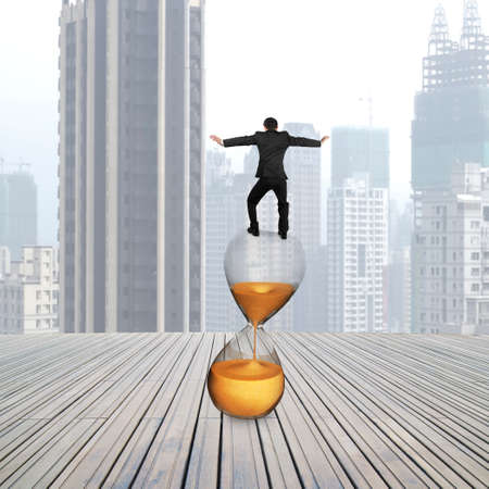 trickling: Rear view of businessman balancing on hourglass, with cityscape background. Stock Photo