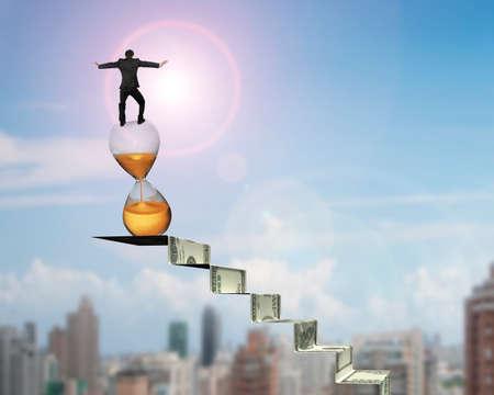 gestion del tiempo: El hombre de negocios de equilibrio de reloj de arena en la parte superior de las escaleras de dinero, con fondo de cielo sol paisaje urbano.