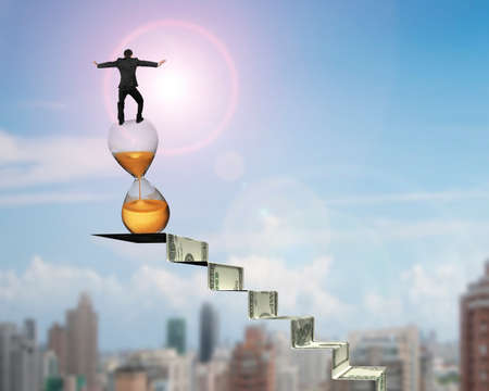 Businessman balancing hourglass on top of money stairs, with sun sky cityscape background.