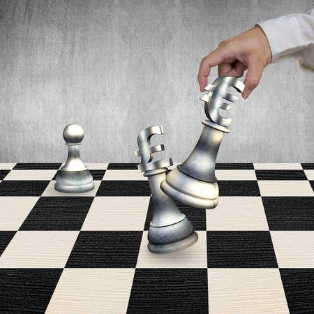 libra esterlina: La mano del hombre que juega el dinero en moneda piezas símbolo de ajedrez, con la muestra euro símbolo de la libra esterlina jaque mate. Foto de archivo