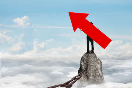 iron chain: Man holding red arrow up sign, standing on mountain peak with rusty iron chain, on sky cloudscape background. Stock Photo