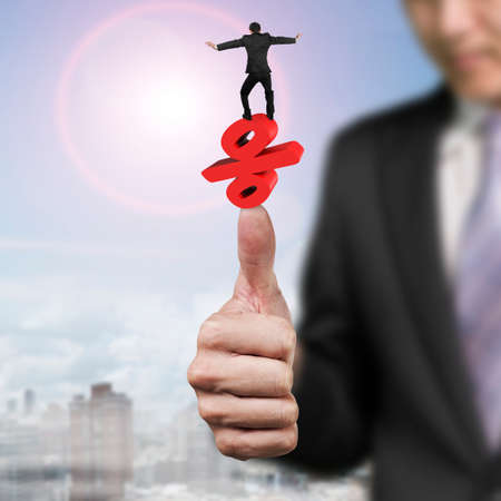 approval rate: Businessman balancing red percent symbol on another man big hand thumb, with sun sky clouds cityscape background.
