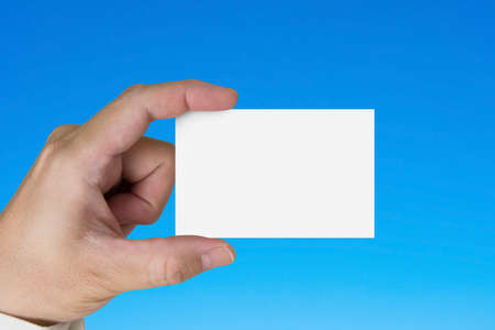 message card: Hand holding blank white name card, isolated on blue background