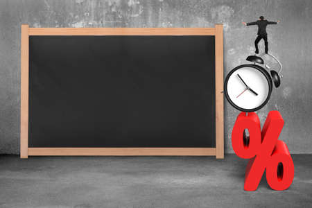 percentage sign: Businessman balancing on alarm clock and red percentage sign, with blank blackboard on concrete wall. Stock Photo