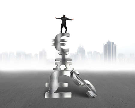 savings risk: Businessman balancing on top of stack money symbols, with gray city buildings skyline background.
