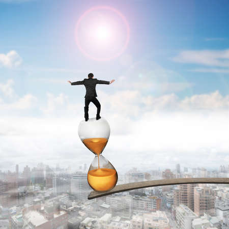 Businessman balancing hourglass on edge of wooden plank, with sun sky cityscape background. Stock Photo