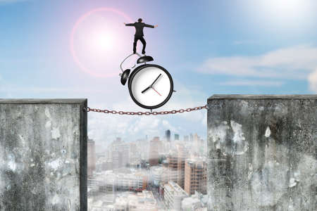 rusty chain: Businessman balancing alarm clock on rusty chain connected two high dirty concrete walls, with sun sky cityscape background.