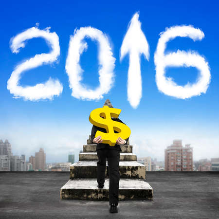 investment vision: Man carrying golden dollar sign climbing old concrete stairs toward white 2016 shape clouds in sky.