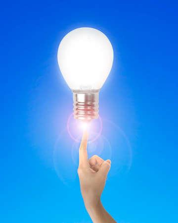 dedo �ndice: El dedo �ndice apuntando al humano con bombilla de luz brillante, sobre fondo azul.