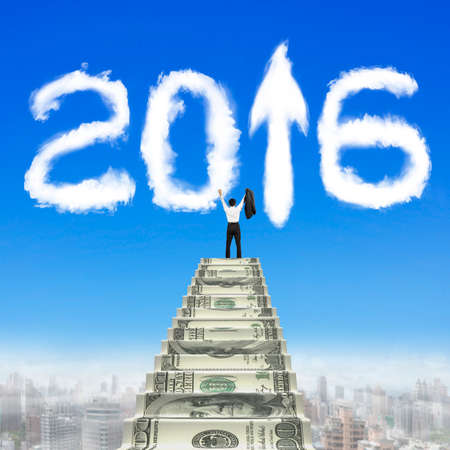 arrow up: Businessman steps up money stairs with white 2016 arrow up shape clouds in blue sky. Stock Photo