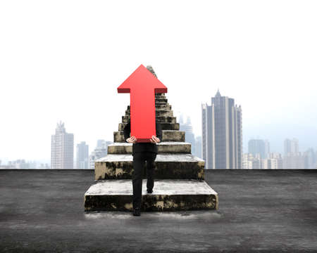 hard work ahead: Man carrying red arrow up sign climbing old concrete stairs, with city skyscraper background