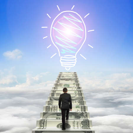 Businessman climbing the money stairs toward light bulb hand drawing, with sun sky cloudscape background.