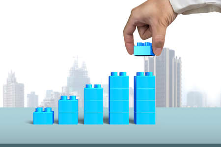 Human hand holding a blue block to complete growth bar graph shape, with city skyscraper background.