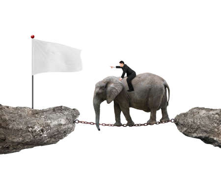 Businessman with pointing finger gesture riding elephant on rusty chain toward white flag on cliff, isolated on white background.