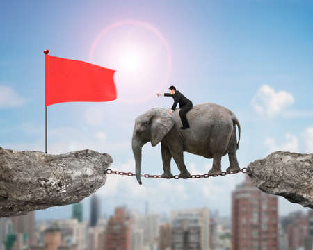 Businessman with pointing finger gesture riding elephant on rusty chain toward red flag on cliff, on sunny sky cityscape background.