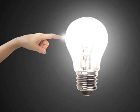 dedo �ndice: El dedo �ndice tocando bombilla humana con la luz brillante, sobre fondo negro.