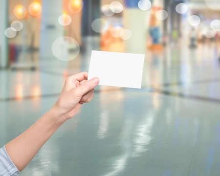 Womna hand holding blank white name card, on blurred background