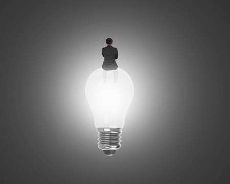 businessman sitting on light bulb with bright white light on black background photo