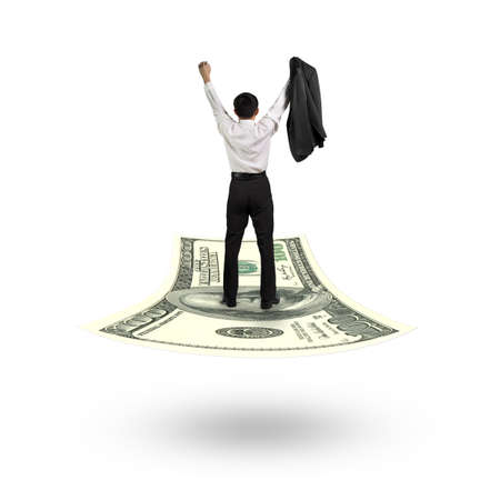 ventures: Rear view businessman cheering and standing on money flying carpet, isolated on white background.