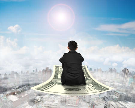 flying man: Rear view businessman sitting on money flying carpet, with sunny sky cityscape background.