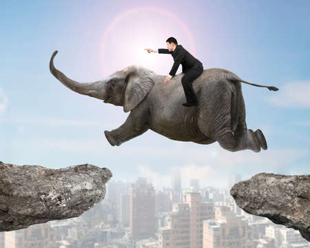 man flying: Man with pointing finger gesture riding elephant flying over two cliffs, with sunny sky cityscape background.
