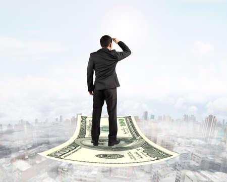 money flying: Vista trasera de negocios de pie en el dinero alfombra voladora y mirando al frente, con fondo de cielo niebla paisaje urbano.