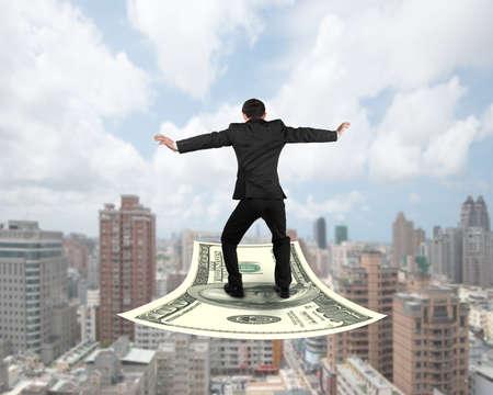 money flying: Vista trasera de negocios que balancea en dinero volando alfombra, con edificios de la ciudad de fondo. Foto de archivo