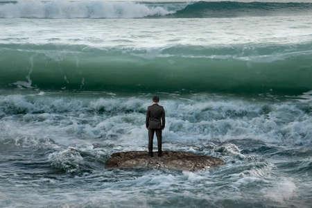 concepto: Vista trasera de negocios de pie sobre la roca en el oc�ano frente a olas que se aproximan