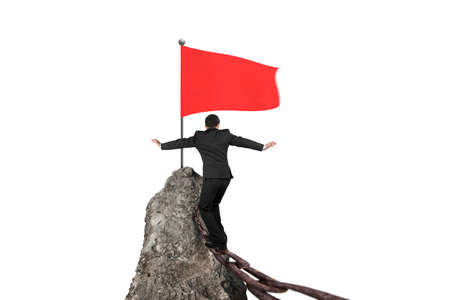 overcome a challenge: Businessman walking and balancing on rusty chain for wavy red flag on top of rocky mountain peak isolated in white background Stock Photo