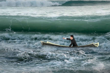 ventures: Businessman with pointing finger gesture sitting on money boat in the ocean with oncoming waves
