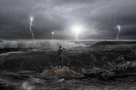 tormenta: Del hombre en roca mirando al faro en el mar con la tormenta, el trueno, alijo y las olas en la oscuridad