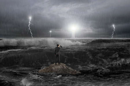 Homme sur un rocher regardant phare dans l'océan avec la tempête, le tonnerre, de transbordement et les vagues dans l'obscurité Banque d'images