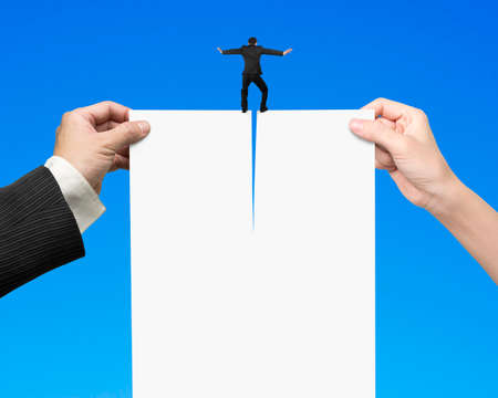 Man and woman hands holding the tearing contract blank white paper with businessman standing on it, isolated on blue.