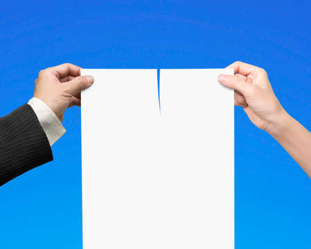 broken contract: Man and woman hands holding the tearing contract paper with blank white, isolated on blue.