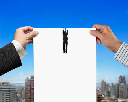 breaking the rules: Two mans hands holding the tearing contract blank white paper with businessman hanging on it, on blue sky and city buildings background.