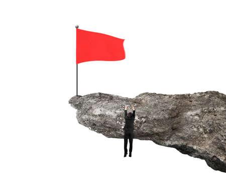 peligro: Hombre de negocios colgado en el acantilado con la bandera ondulada de color rojo en la parte superior aislado en el fondo blanco